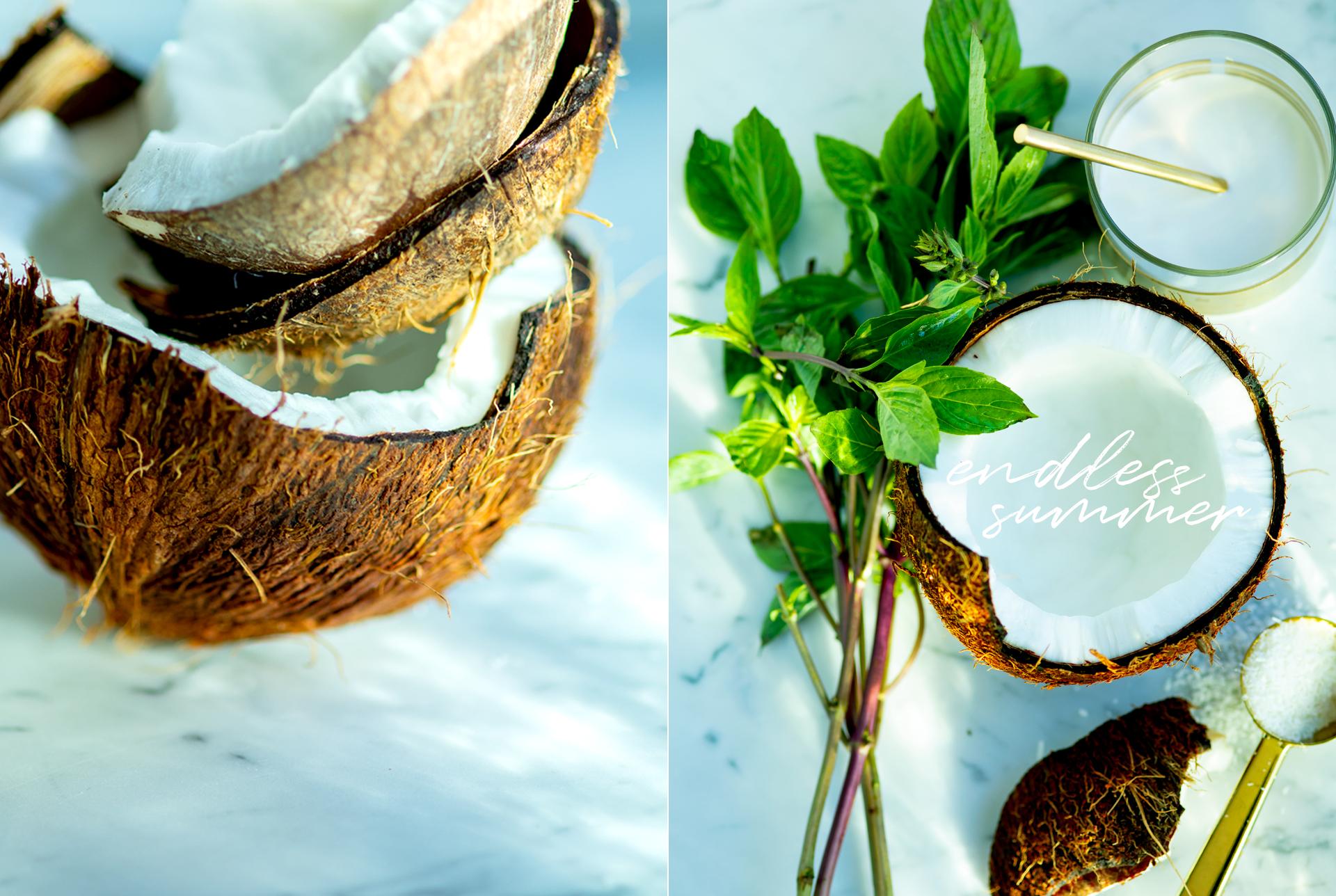 Nahaufnahme von einer aufgebrochenen Kokosnuss. geoeffnete Kokosnuss mit einem Glas Kokosmilch, einen Loeffel mit Kokosraspeln und einen Bund ThaiBasilikum - Foodfotografie Muenchen