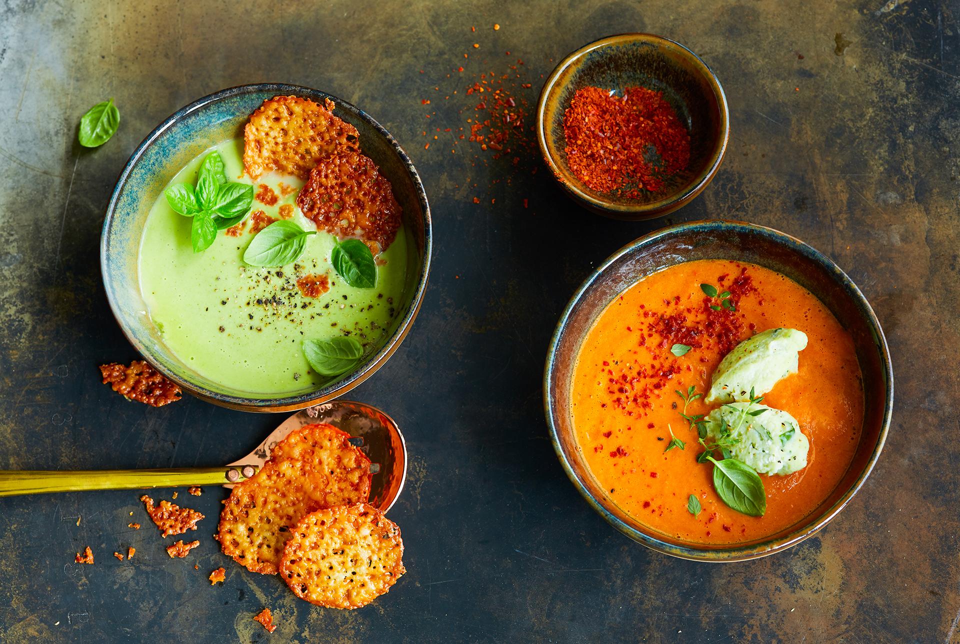 Schale mit Erbsensuppe und Tomatensuppe. Dazu Käsecracker, Chilischoten und Nocken. fotografiert von Foodphotography Katrin Winner