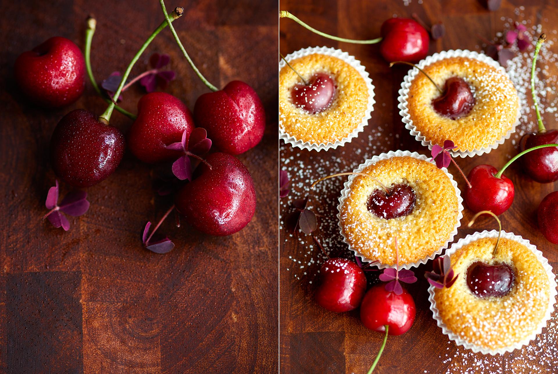 Kirschen mit Sauerklee auf einem dunklen Holzuntergrund. Financier mit Kirschen verziert mit Sauerklee und Puderzucker - Foodphotography Katrin Winner