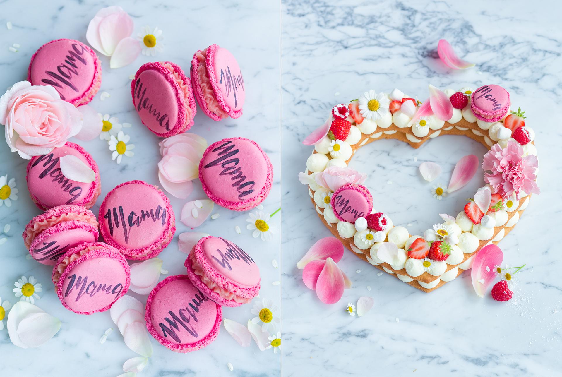 Cake Lettering - rosa Macarons mit Mama-Schriftzug und essbaren Bluetenblaettern. Kuchen in Herzform mit Sahne-Creme-Tupfen, essbaren Blueten, Himbeeren und rosa Macarons mit Mama-Schriftzug fotografiert von Foodphotography Katrin Winner