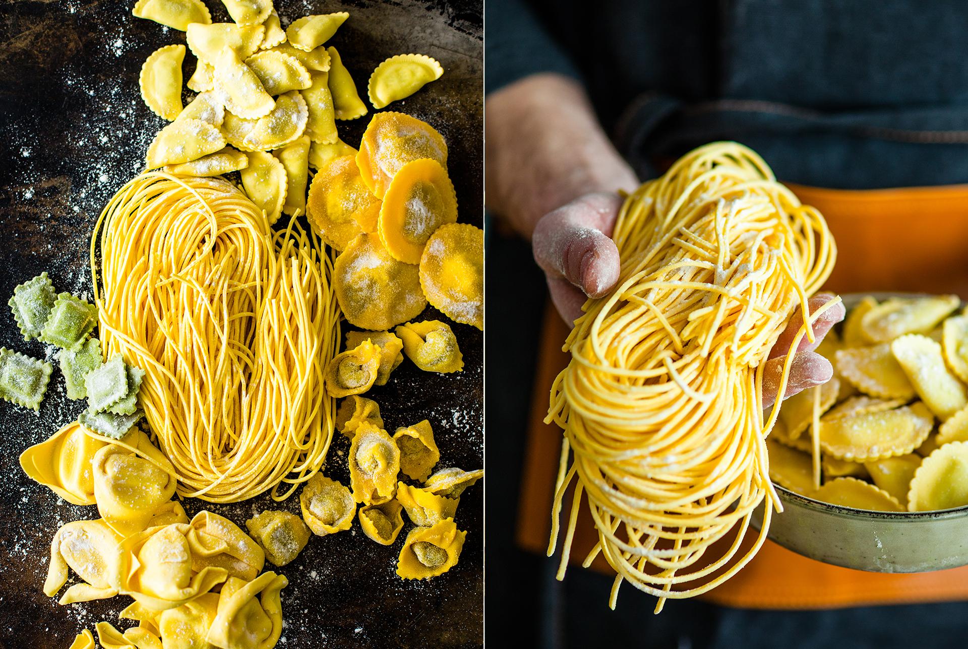 Stillleben mit verschiedene Pastasorten mit Mehl auf dunklem Untergrund. Person haelt Spaghetti und eine Schale mit Ravioli. Fotografiert von Katrin Winner Foodfotografie Muenchen
