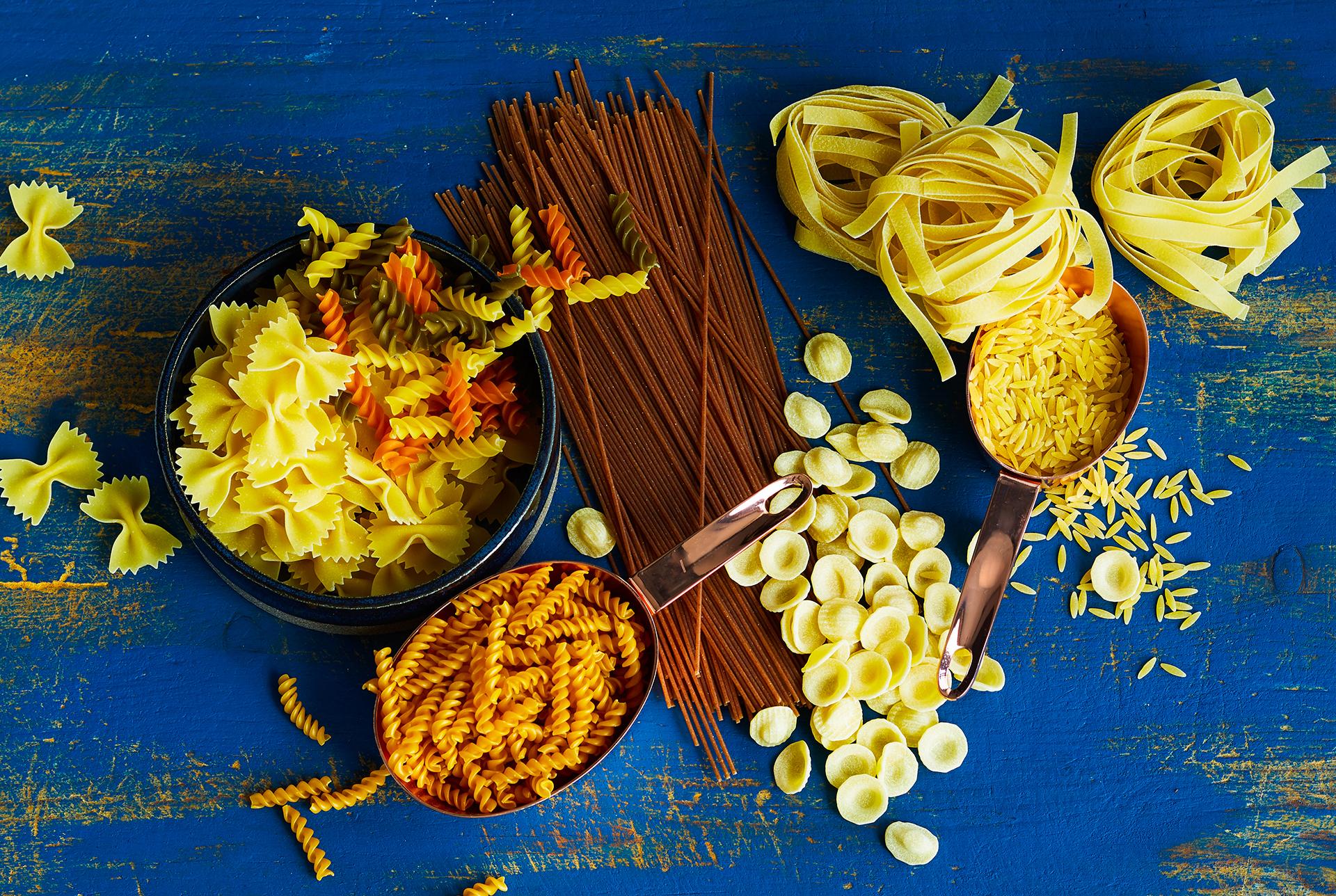 verschiedene Nudelsorten auf dunkelblauen Holzbrett. Farfalle, Spirelli, Spaghetti, Tagliatelle, Kritharaki, Orecchiette, Kichererbsennudeln, Linsennudeln fotografiert von Katrin Winner