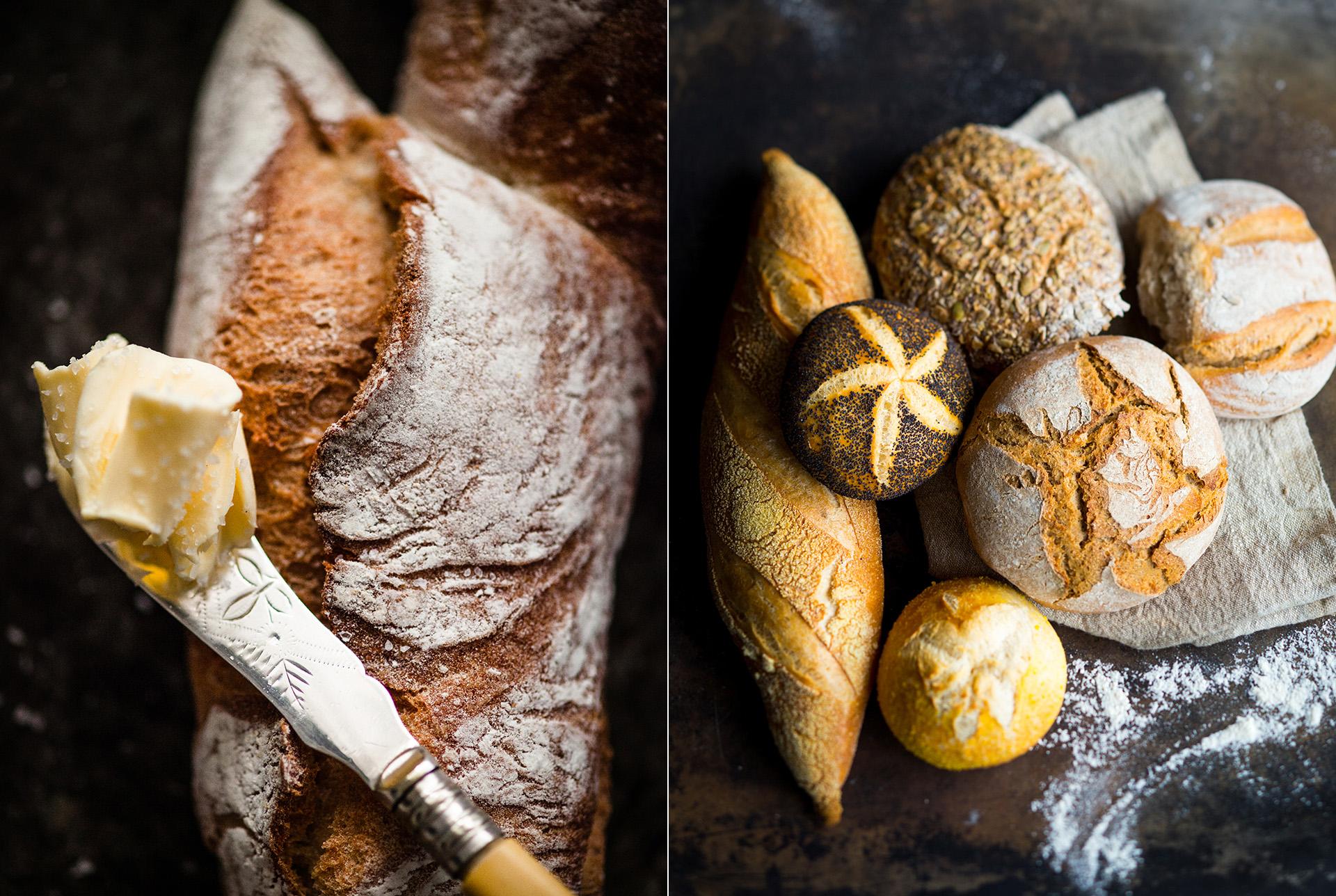 Nahaufnahme eines Brotes mit einem Messer mit Butter. Arrangement mit mehreren verschiedenen Brot- und Semmelsorten auf dunklem Untergrund